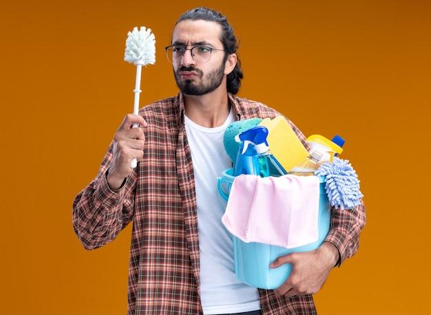 Denkender junger hübscher reinigungsmann, der t-shirt trägt, eimer mit reinigungswerkzeugen hält und pinsel in seiner hand lokalisiert auf orange wand betrachtet