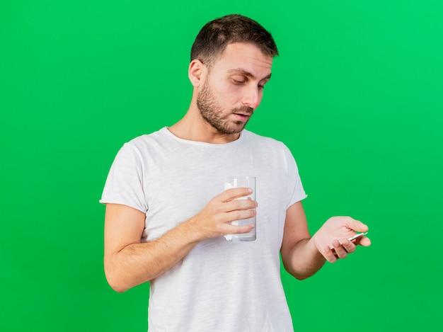 Denkender junger kranker mann, der glas wasser hält und pillen in seiner hand lokalisiert auf grünem hintergrund betrachtet