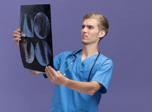 Denkender junger männlicher arzt, der arztuniform mit stethoskop hält und röntgenstrahl auf blauer wand isoliert betrachtet