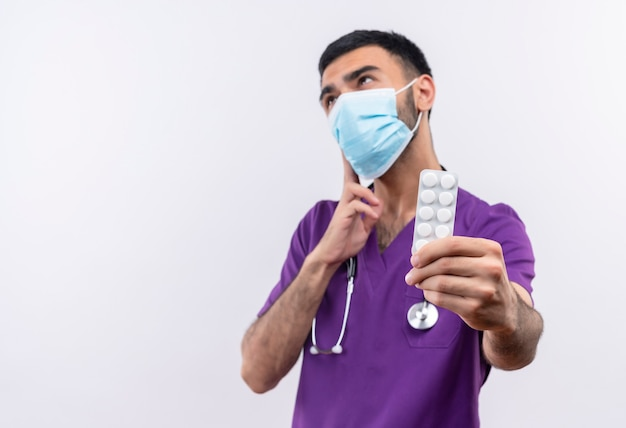 Denkender junger männlicher arzt, der lila chirurgenkleidung und medizinische stethoskopmaske trägt, die pillen auf isoliertem weiß heraushalten