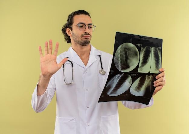 Denkender junger männlicher arzt mit optischer brille, die weiße robe mit stethoskop hält, das röntgen hält und betrachtet, das stoppgeste auf grün zeigt