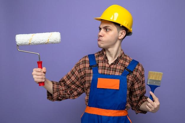 Denkender junger männlicher baumeister, der eine uniform trägt und einen pinsel hält, der in seiner hand auf die bürste schaut?