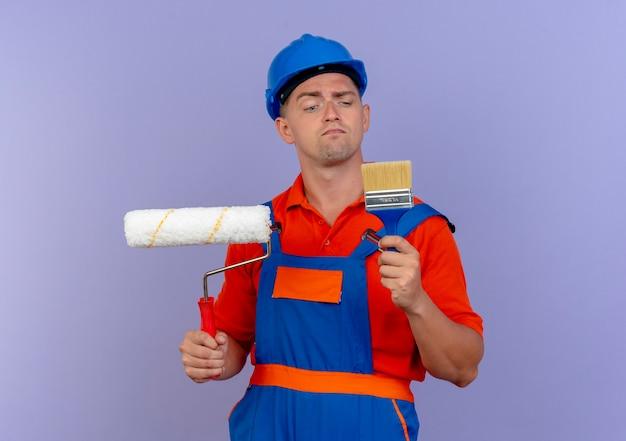 Denkender junger männlicher baumeister, der uniform- und schutzhelm trägt, der farbroller hält und pinsel in seiner hand auf purpur betrachtet