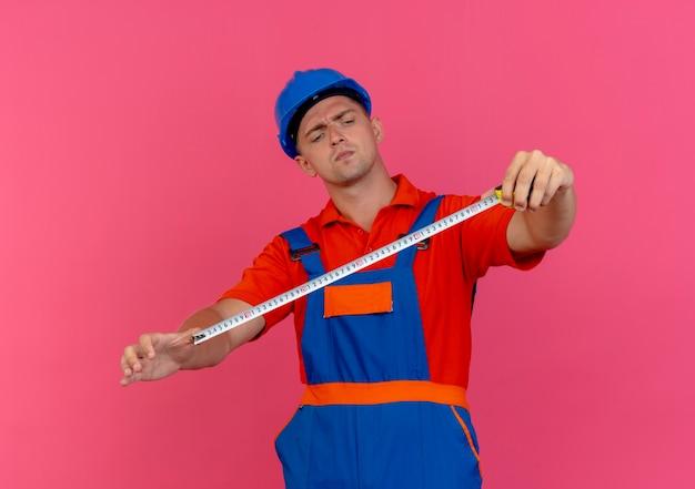 Denkender junger männlicher baumeister, der uniform und schutzhelm trägt, der meterband hält und betrachtet
