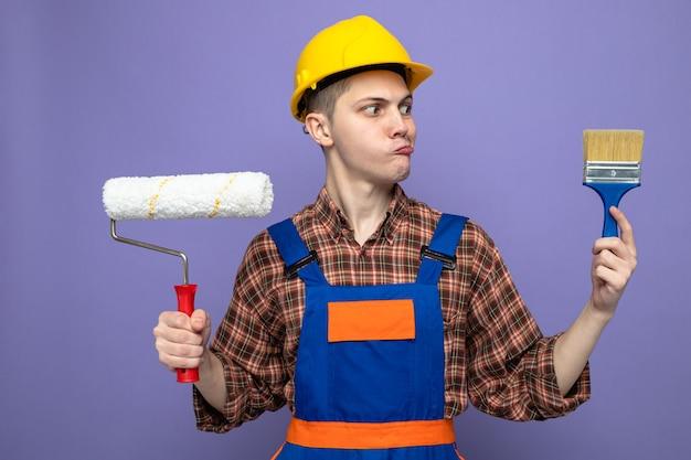 Denkender junger männlicher baumeister in uniform, der pinsel mit walzenbürste hält