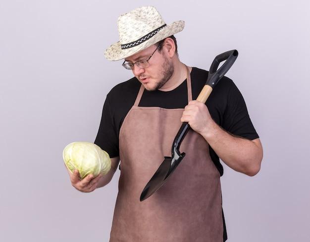 Denkender junger männlicher gärtner, der gartenhut trägt, der spaten auf schulter setzt und kohl in seiner hand lokalisiert auf weißer wand betrachtet