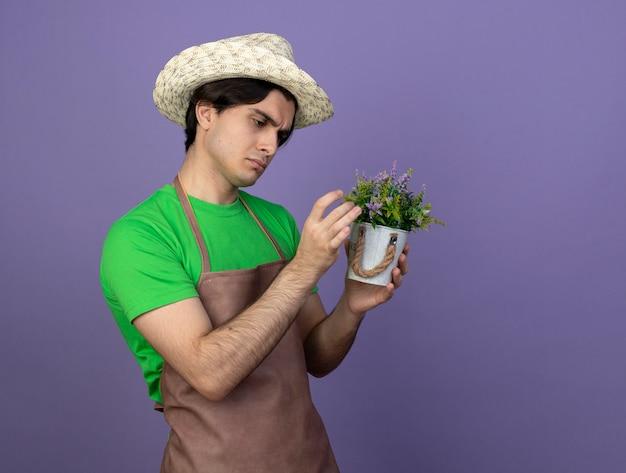 Denkender junger männlicher gärtner in der uniform, die gartenhut hält und blume im blumentopf betrachtet