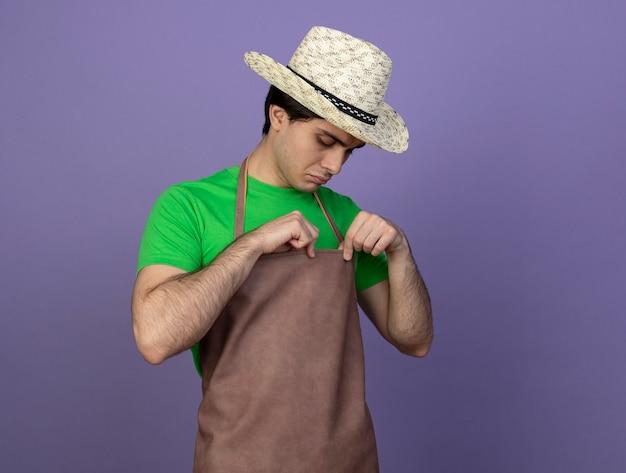 Denkender junger männlicher gärtner in der uniform, die gartenhut hält und uniform betrachtet