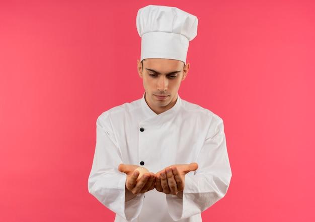 Denkender junger männlicher koch, der kochuniform trägt, die eier in seinen händen mit kopienraum betrachtet