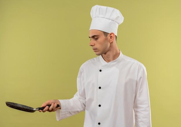 Denkender junger männlicher koch, der kochuniform trägt, die pfanne in seiner hand mit kopienraum betrachtet