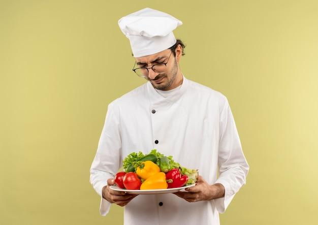 Denkender junger männlicher koch, der kochuniform und gläser hält und gemüse auf platte lokalisiert auf grüner wand hält