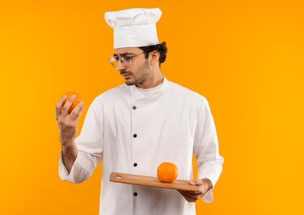 Denkender junger männlicher koch, der kochuniform und gläser hält und orange auf schneidebrett lokalisiert auf gelber wand hält und betrachtet
