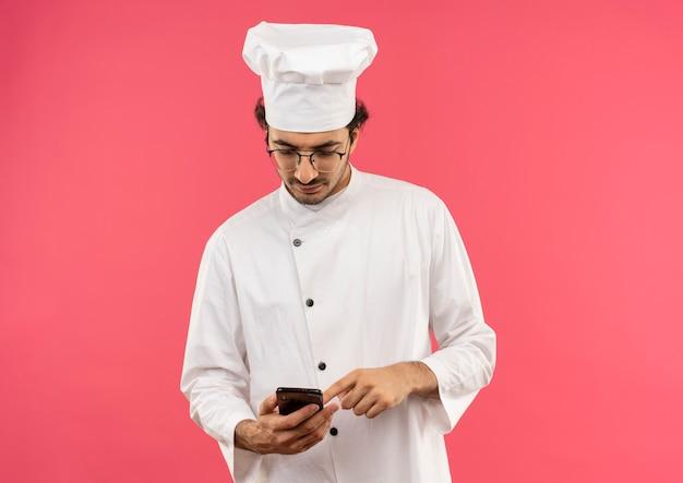 Denkender junger männlicher koch, der kochuniform und gläser hält und telefon lokalisiert auf rosa wand hält