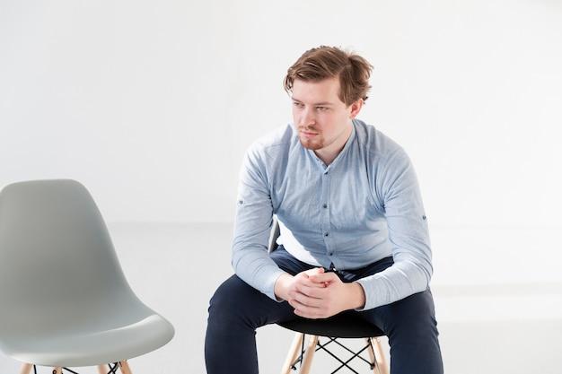 Denkender junger mann, der auf einem stuhl sitzt