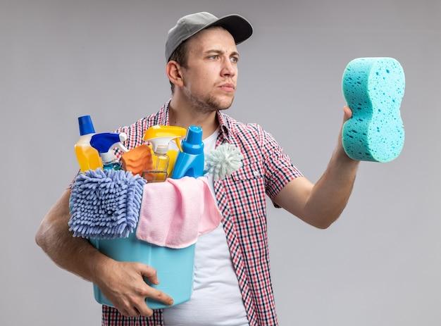 Denkender junger mann, der eine kappe trägt, die einen eimer mit reinigungswerkzeugen hält und den reinigungsschwamm in seiner hand isoliert auf der weißen wand betrachtet?