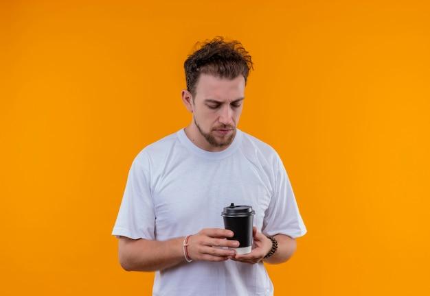 Denkender junger mann, der weißes t-shirt trägt, das tasse kaffee auf seiner hand auf isolierter orange wand betrachtet