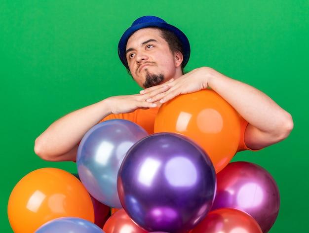 Denkender junger mann mit partyhut, der hinter luftballons steht, isoliert auf grüner wand