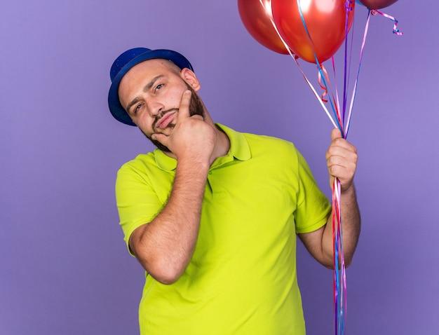 Denkender junger mann mit partyhut, der luftballons hält und das kinn packte