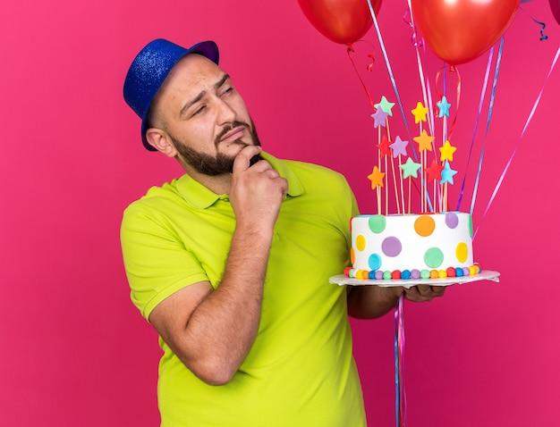 Denkender junger mann mit partyhut isoliert auf luftballons mit kuchen packte das kinn isoliert auf rosa wand