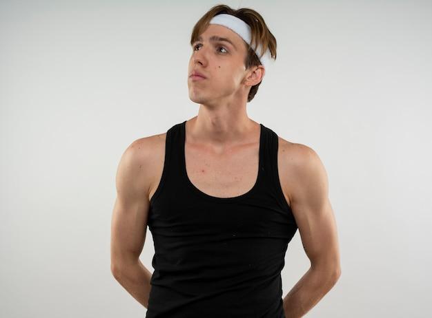 Denkender junger sportlicher kerl, der seite betrachtet, die stirnband und armband hält, die hände auf taille lokalisiert auf weißer wand halten