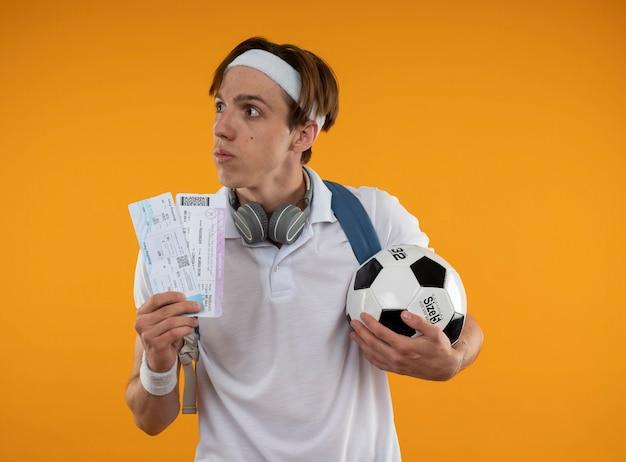 Denkender junger sportlicher kerl, der stirnband mit armband und rucksack mit kopfhörern am hals trägt, der tickets mit ball lokalisiert auf gelber wand hält