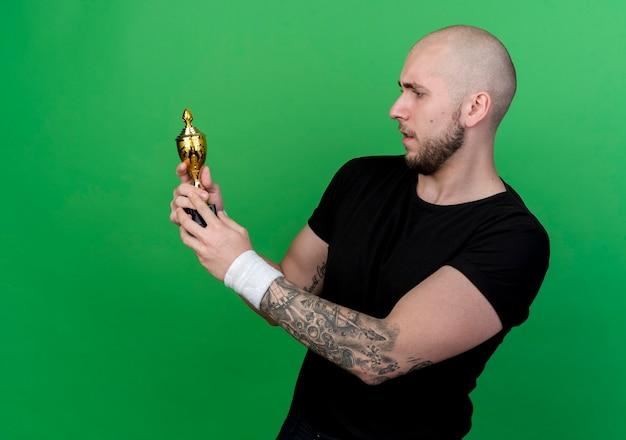 Denkender junger sportlicher mann, der armband hält und gewinnerpokal lokalisiert auf grün hält