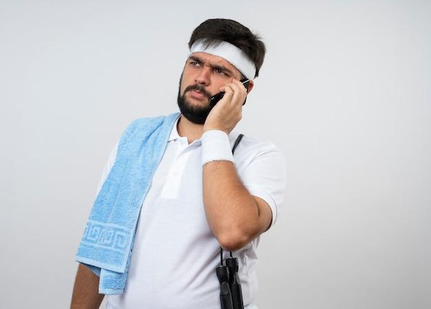 Denkender junger sportlicher mann, der seite betrachtet, die stirnband und armband mit handtuch und springseil auf schulter trägt, spricht am telefon lokalisiert auf weißer wand mit kopienraum