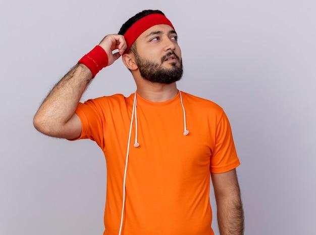 Denkender junger sportlicher mann, der seite betrachtet, die stirnband und armband mit kopfhörern auf schulterkratzkopf lokalisiert auf weißem hintergrund trägt