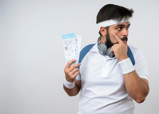 Denkender junger sportlicher mann, der seite betrachtet, die stirnband und armband mit rucksack hält, der tickets hält, die hand auf gesicht lokalisiert auf weißer wand mit kopienraum setzen