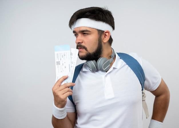 Denkender junger sportlicher mann, der seite betrachtet, die stirnband und armband mit rucksack in kopfhörern trägt, die tickets lokalisiert auf weißer wand halten