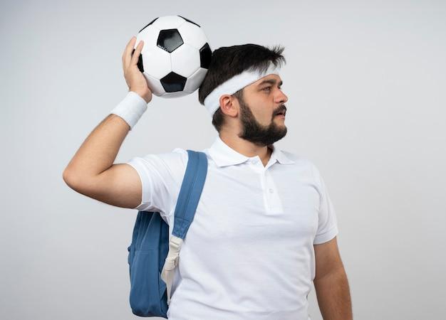 Denkender junger sportlicher mann, der seite betrachtet, die stirnband und armband mit rucksack trägt, der ball auf kopf lokalisiert auf weißer wand setzt