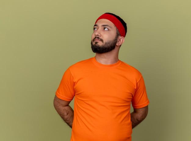 Denkender junger sportlicher mann, der seite betrachtet, die stirnband und armband trägt und hände auf taille hält