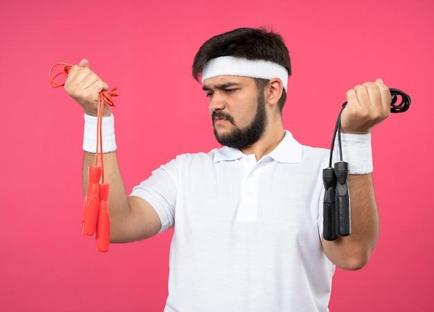 Denkender junger sportlicher mann, der stirnband und armband hält, die springseile hält und betrachtet, die auf rosa wand lokalisiert werden