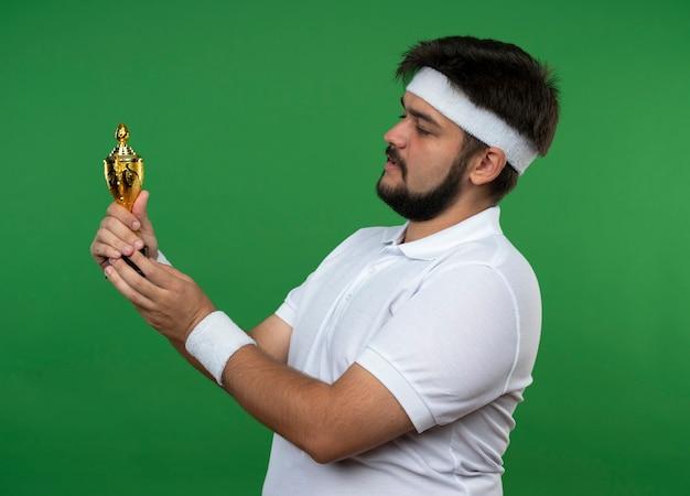 Denkender junger sportlicher mann, der stirnband und armband hält und siegerpokal lokalisiert auf grüner wand hält