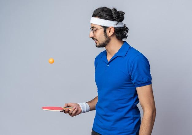 Denkender junger sportlicher mann mit stirnband mit armband, der einen tischtennisball auf dem schläger hält und betrachtet