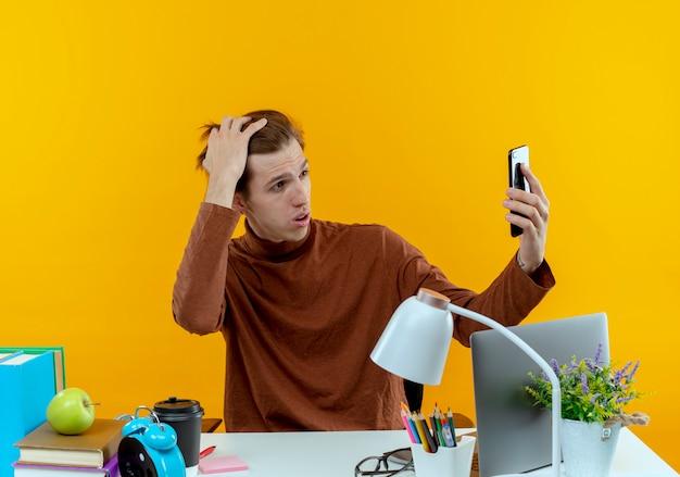 Denkender junger studentenjunge, der am schreibtisch sitzt