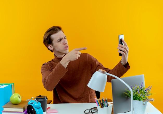 Denkender junger studentjunge, der mit schulwerkzeugen am schreibtisch sitzt, macht ein selfie und zeigt ihnen geste auf gelb