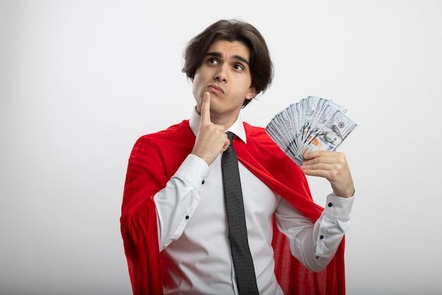 Denkender junger superhelden-typ, der seite betrachtet, die krawatte hält, die bargeld hält und finger auf mund lokalisiert auf weißem hintergrund setzt