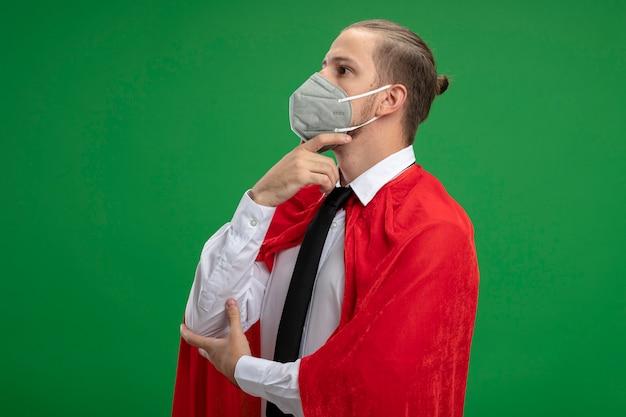 Denkender junger superheldenmann, der krawatte mit medizinischer maske trägt, die seite betrachtet, die hand unter kinn lokalisiert auf grünem hintergrund setzt