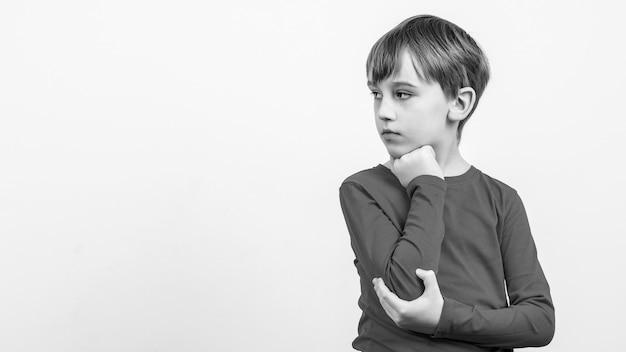 Denkender kleiner junge, der lokal über weißem hintergrund steht. zur seite schauen.