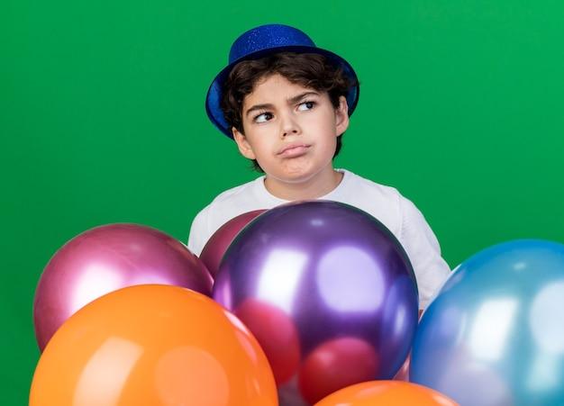 Denkender kleiner junge mit blauem partyhut, der hinter luftballons steht, isoliert auf grüner wand