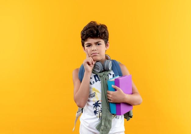 Denkender kleiner schuljunge, der rückentasche und kopfhörer hält, bücher hält und hand auf wange lokalisiert auf gelb legt