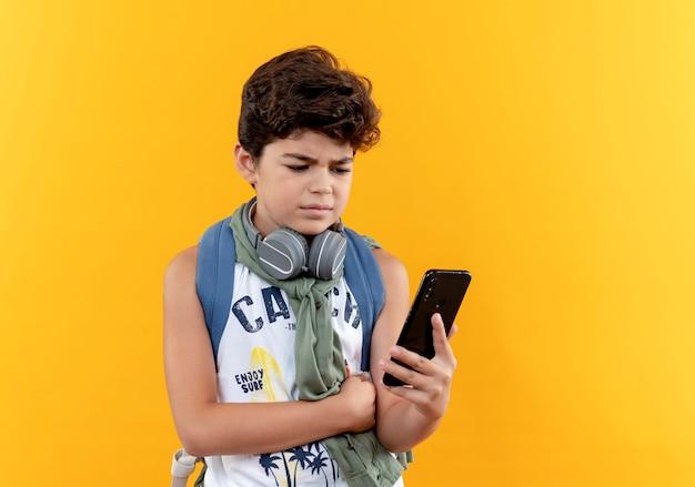 Denkender kleiner schuljunge, der rückentasche und kopfhörer trägt und telefon lokalisiert auf gelber wand hält