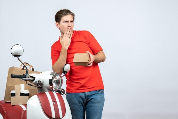 Denkender lieferbote in der roten uniform, die nahe roller hält, der kleine box auf weißem hintergrund hält