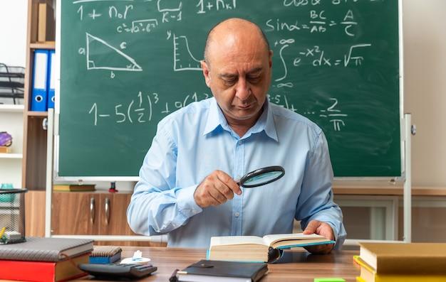Denkender männlicher lehrer mittleren alters sitzt am tisch mit schulmaterial und liest ein buch mit lupe im klassenzimmer