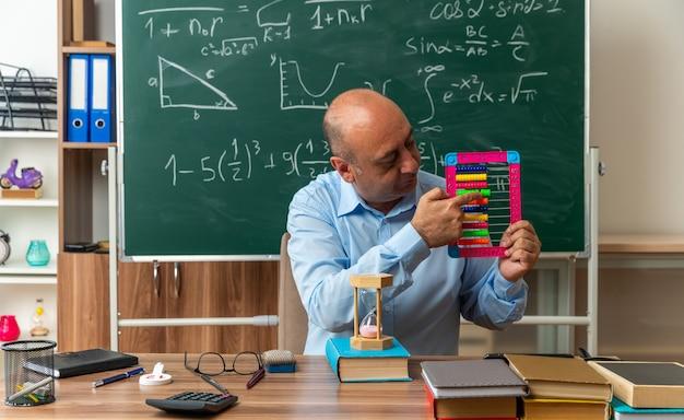 Denkender männlicher lehrer mittleren alters sitzt am tisch mit schulsachen und zeigt auf abakus im klassenzimmer