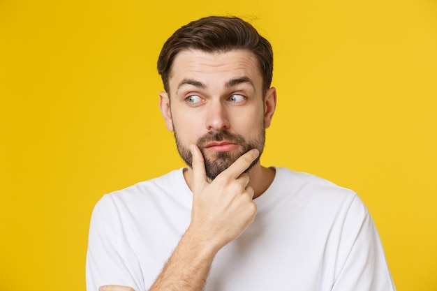 Denkender mann getrennt auf gelb. nahaufnahmeporträt eines zufälligen jungen nachdenklichen mannes, der oben copyspace betrachtet. kaukasisches männliches baumuster.