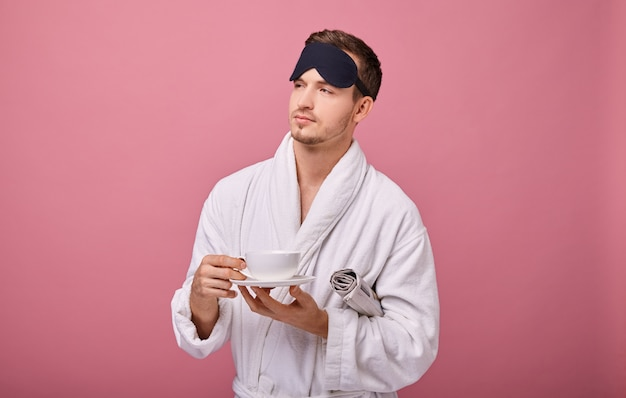 Denkender mann in schlafmaske auf seinem kopf im weißen mantel mit zeitung unter seinem arm aufgewacht und lächelte an der kamera mit tasse kaffee in den händen.