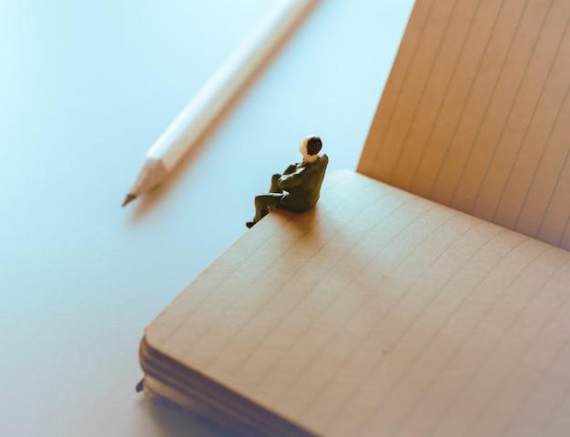 Denkender mann, miniaturmann, der alleine auf notizbuch sitzt.
