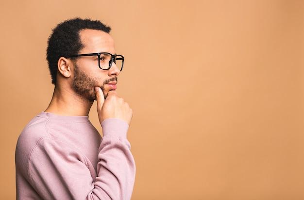 Denkender mann mit ernstem ausdruck, der schaut, isoliert gegen beige posiert.